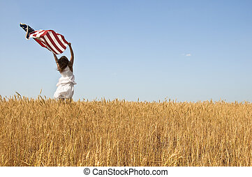 Beautiful young girl holding an American flag in the wind in...