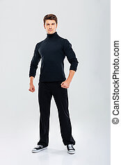 Full length of strong young man in black clothes standing -...