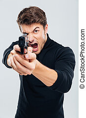 Angry irritated young man aiming gun on you and shouting