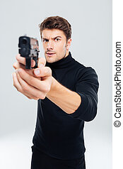 Concentrated young man standing and pointing with gun on you...