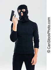 Criminal man in balaclava standing and holding gun
