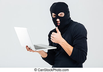 Man in balaclava using laptop and showing thumbs up