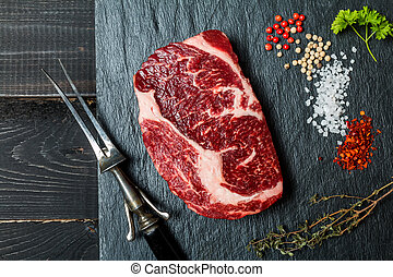 Raw fresh meat ribeye steak, chili pepper, salt and thyme on...