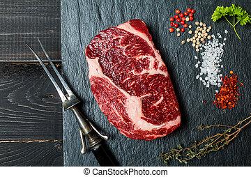 Raw fresh meat ribeye steak, chili pepper, salt and thyme on...