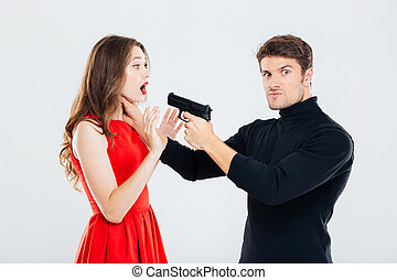 Angry man choking and threatening with gun to woman
