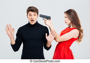Woman standing and threatening with gun to scared young man...