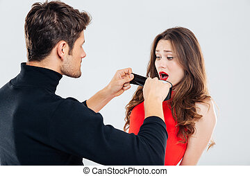 Criminal man covering mouth of scared woman with black tape