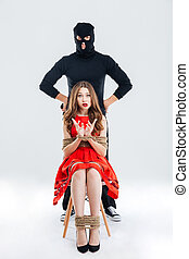 Man in balaclava and frightened young woman bounded with ropes
