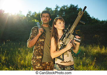 White girl and an Arab man in camouflage with a weapon in...