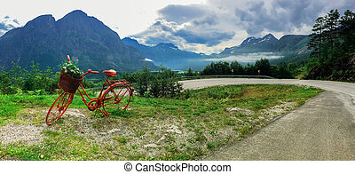 Lonely red decorative bicycle stands on a hillside,...