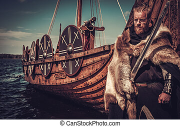Viking warrior with sword and shield standing near Drakkar...