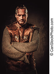 Angry viking in a traditional warrior clothes, posing on a...
