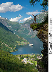 Man hiker enjoying scenic landscapes at a cliff edge,...