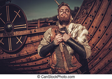 Viking warrior with axes standing near Drakkar on the...