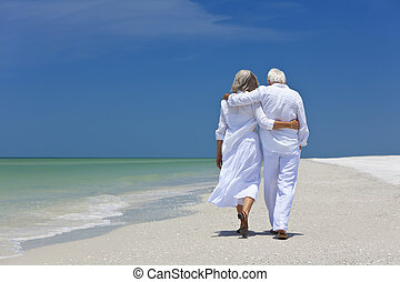 Rear View of Senior Couple Walking Alone on A Tropical Beach...