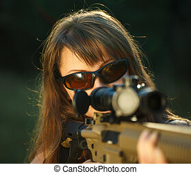 Girl with a gun for trap shooting and shooting glasses...