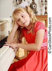 Girl sitting at the piano - Sad little girl in a long orange...