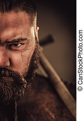 Angry viking with ax in a traditional warrior clothes,...