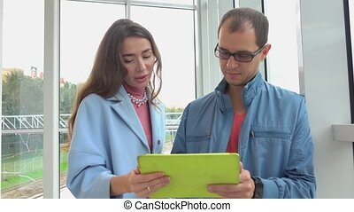 Cheerful man and brunette girl using tablet computer at...
