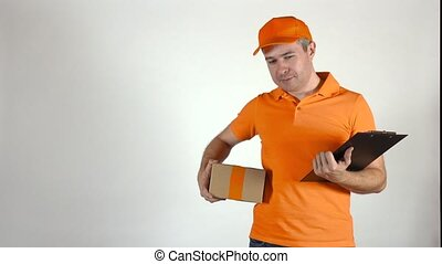 Delivery man in orange uniform giving a small parcel. Light...