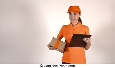 Beautiful female courier in orange uniform delivering a...