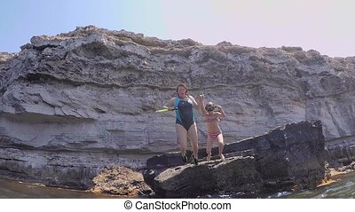 Mother and daughter jumping off a cliff into the water....