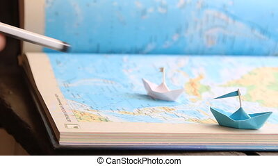 travel, travelling or tourism concept, paper boats on the sea atlas