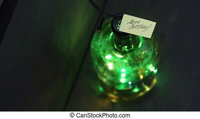 Merry Christmas - calligraphic inscription and colored lights in a bottle.