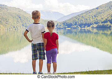 Little boy and girl standing holding hands on the bank of a lake