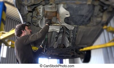 Exhaust of a car on bridge at auto repair shop with a...