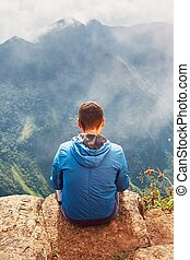 Tourist in mountains. Young man sitting on the place which...