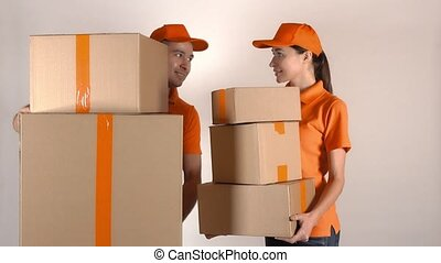 Male and female couriers in orange uniform delivering multiple cartons. Light gray backround, 4K studio shot