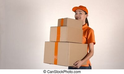 Beautiful girl in orange courier uniform delivering a stack...