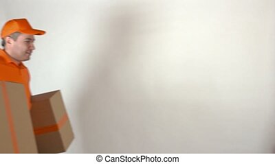 Delivery man in orange uniform delivering two big cartons. Light gray backround, 4K studio shot