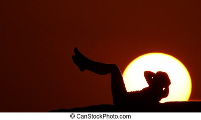 woman crunching at sunset huge sun.mov
