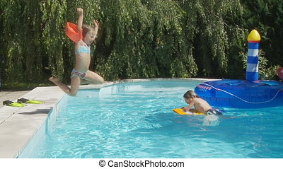 girl jumping in pool slo mo - boy in swimming pool little...