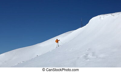 falling skier part III - male skier putting on his ski and...