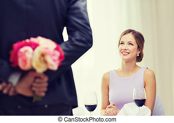 young woman looking at man with flower bouquet - restaurant,...