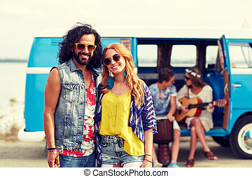 smiling hippie couple with friends over minivan - summer...