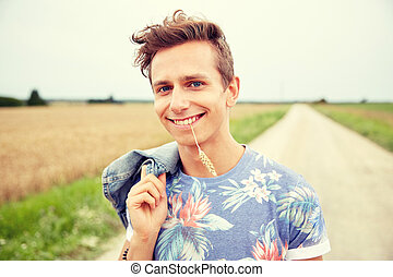 smiling young hippie man on country road - nature, summer,...