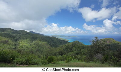 pan shot over tropical mountains on island on cloudy day
