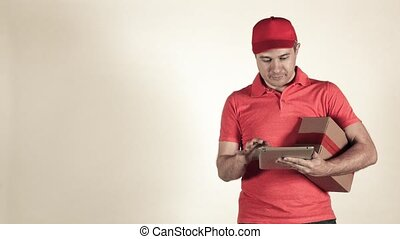 Delivery man in red uniform giving a small parcel. Light gray backround, 4K studio shot