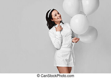 Beautiful fashion model girl with white balloons