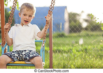 Young boy playing on swings in sunny summer day
