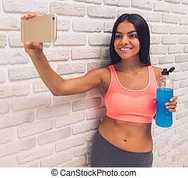 Beautiful young sportswoman in sportswear is making a selfie...