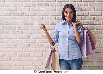 Beautiful young girl in casual clothes is holding shopping...