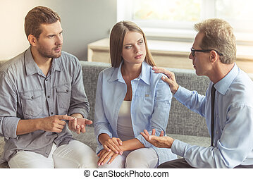 Couple at the psychotherapist - Young couple is holding...