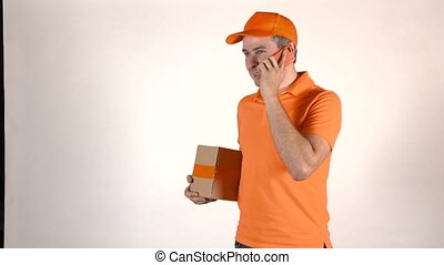 Handsome courier in orange uniform talking on his mobile phone and delivering a parcel. Light grey backround, 4K studio lighting shot