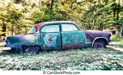 Abandoned car rusting in a field