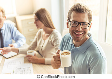 Couple visiting realtor - Handsome young man in glasses is...
